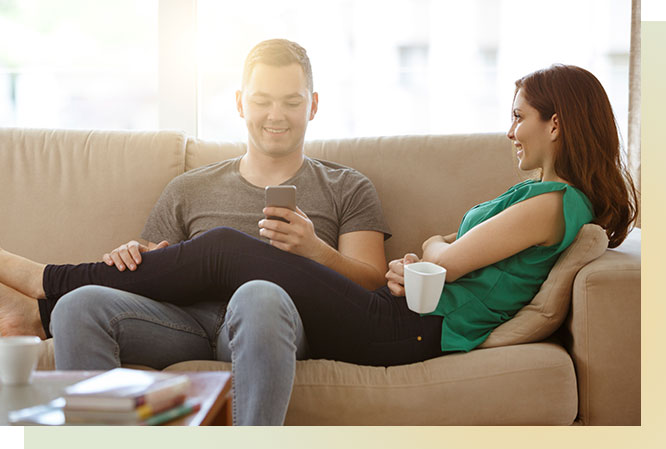 Man and woman sitting on couch. Woman is holding a coffee mug and man is using phone